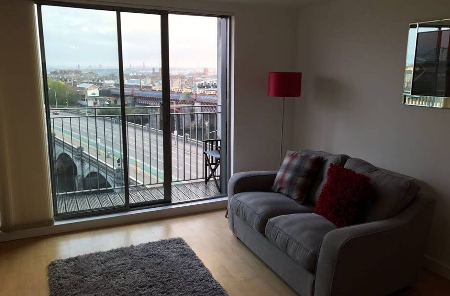 livingroom of glasgow aprtment with balcony and river clyde view